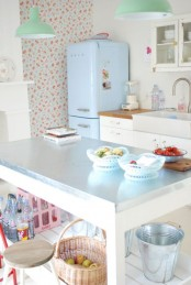 a cute vintage kitchen with floral wallpaper, white cabinets, a fireplace, a large table kitchen island, a blue fridge, mint green pendant lamps and touches of pink