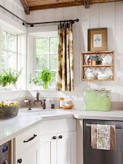 a chic vintage kitchen with white cabinets, white stone countertops, potted greenery, a lovely shelf, printed textiles