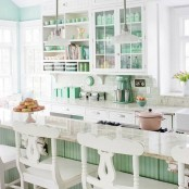 a very chic and cute vintage kitchen done in mint green and white, with glass and open cabinets, a green kitchen island and vintage carved stools is perfect