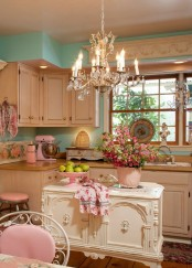 a fabulous vintage kitchen with neutral cabinets, a crystal chandelier, a refined white kitchen island, touches of pink and floral prints