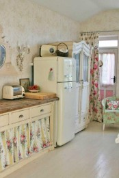 a cute vintage and shabby chic kitchen with white cabinets, a green floral chair and other textules, butcherblock countertops and vintage accessories