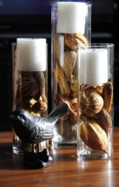 tall glasses with dried fall leaves and pumpkins plus white candles on top