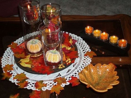 simple fall coffee table decor with candles, fake leaves, fake pumpkins and leaf bowls