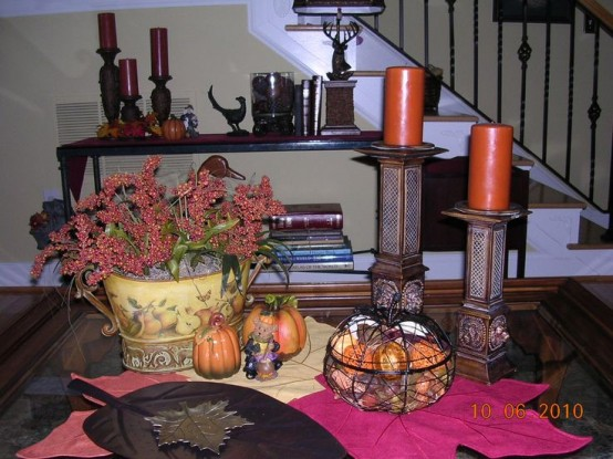 rust candles, fake pumpkins, a bold floral arrangement and leaf bowls for traditional fall coffee table decor