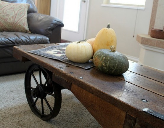 an uncovered coffee table with three natural pumpkins is a cool rustic option for fall home decor