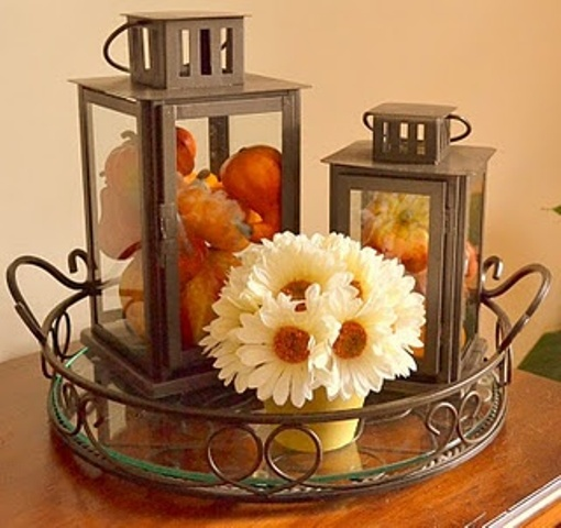 an exquisite tray with two large lanterns filled with blooms and pumpkins and a neutral floral arrangement