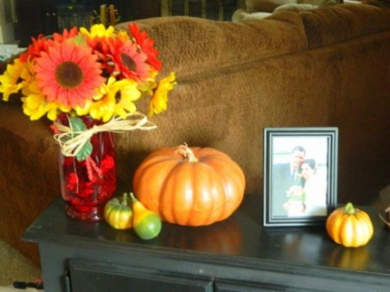 a bright fall flower arrangement with colorful fall pumpkins will be nice for styling your coffee table