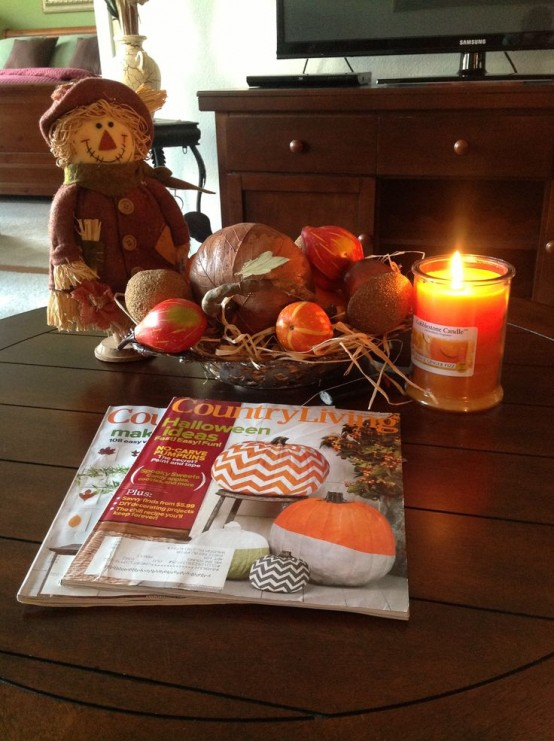 a scarecrow, a fall scented candle, a tray with hay and faux pumpkins for a rustic touch in your space