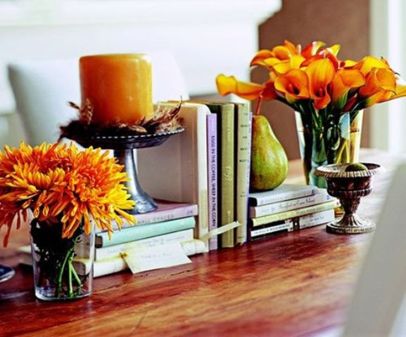a bright orange candle and bright orange fall floral arrangements can be used anywhere for fall home decor