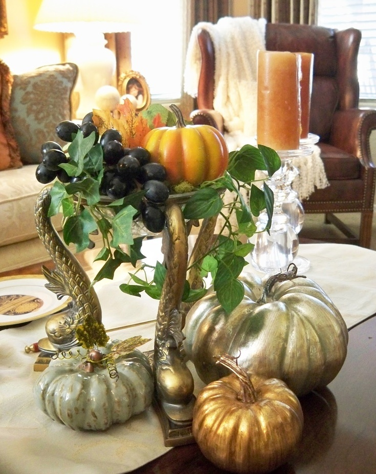 an elegant metal stand with greenery, fresh grapes, fall leaves and bright and metallic faux pumpkins plus candles