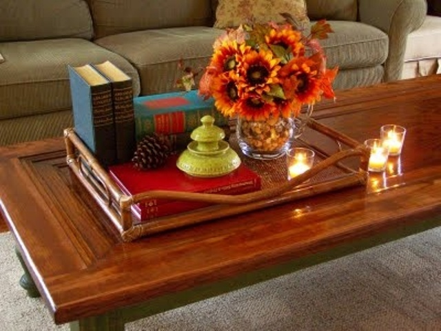 a tray with pinecones and a bright floral arrangement is all that you need for fall coffee table styling