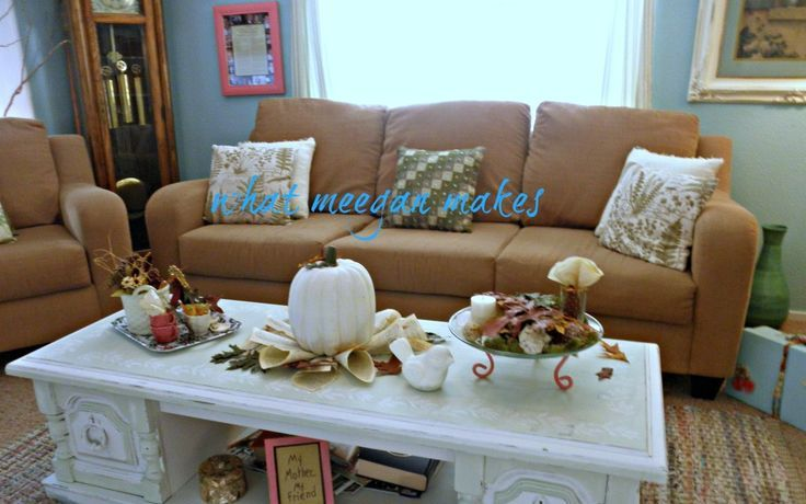 a white pumpkin on leaves, porcelain birds, fall leaves and twigs to decorate the coffee table