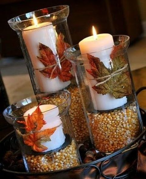 a tray with tall candles filled with corn and white candles with leaves attached to them
