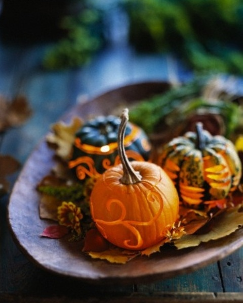 a bowl with fall leaves, blooms and candle lanterns made of little pumpkins is a cool centerpiece or decoration