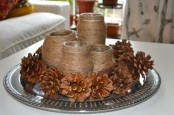 a tray with pinecones and twine wrapped vases or candleholders is a cool and simple rustic decoration