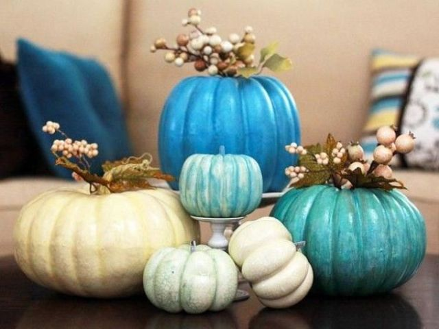 an arrangement of neutral and bright blue pumpkins, berries and little flowers for a centerpiece or decoration