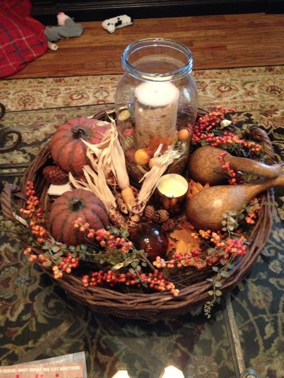a woven tray with corn and corn husks, berries, faux pumpkins and pears plus a candle in the center