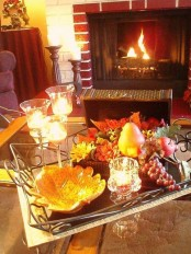 a fall coffee table with candles, a sivler tray with a leaf bowl and fake fruits that look rather natural