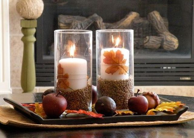 a fall coffee table arrangement with a tray, fall leaves, acorns and apples plus a couple of candles in candle holders