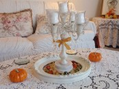 a fall coffee table with pumpkins and a tray with colorful pebbles and a candelabra for a cool and chic look