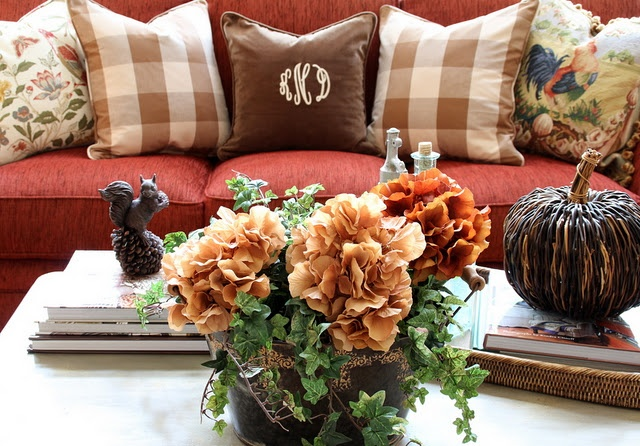 a bright fall floral attangement, a squirrel figurine and a woven pumpkin for cozy fall table decor