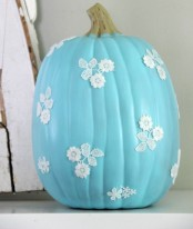 a blue pumpkin with white lace flowers attached looks super cute and fun, such a color will make a statement