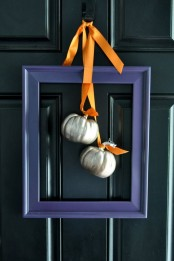 a modern alternative to a fall wreath – a purple frame with metallic pumpkins and orange ribbons is very stylish and bold