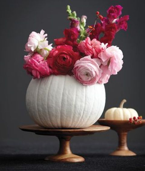 a white pumpkin used as a vase for red and light pink blooms will be a bold and gorgeous fall centerpiece