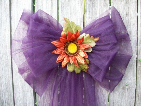 a purple tulle bow with bright blooms is a bright alternative to a fall wreath and will last long