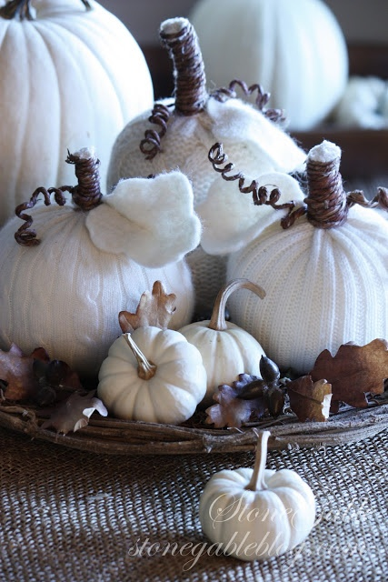 white faux, knit and crocheted pumkins, acorns and leaves compose an unusual and very cozy fall centerpiece