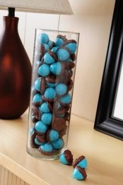 blue acorns in a tall glass vase are a nice and bright fall decoration to go for