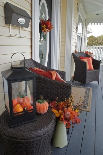 Stuff a lantern with pumpkins and put it on a table on your porch. YOu've got yourself a simple yet stylish seasonal display.