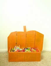 an orange pumpkin-shaped stand with candies is a cool decoration for outdoors and can be a fit for your entryway, too