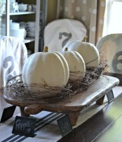 a wooden stand with white pumpkins covered with vine is a rough rustic decoration or centerpiece