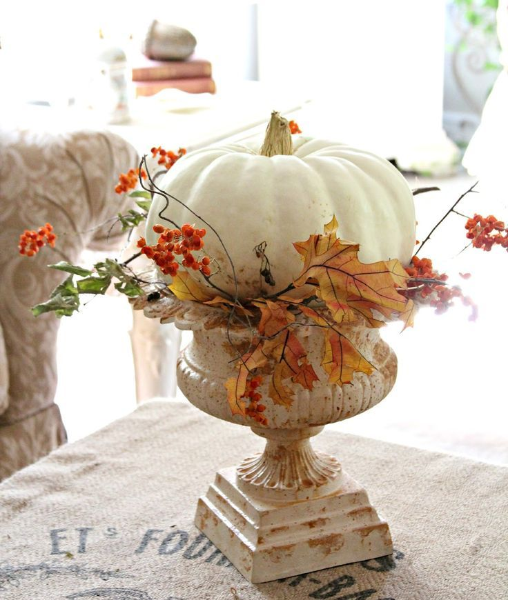 a large white pumpkin with faux berries and leaves placed into a white vintage urn as a pumpkin stand is chic
