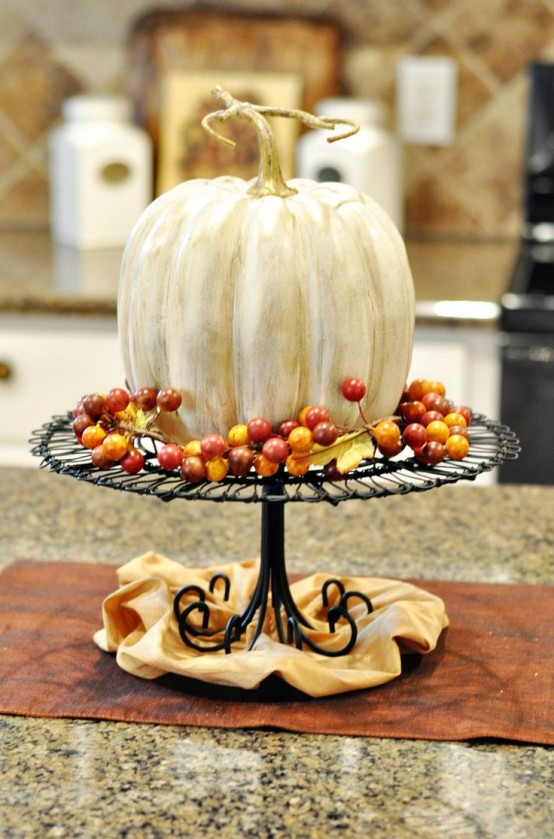 a metal stand with a faux white pumpkins and some faux berries is a classic fall decoration for a rustic feel