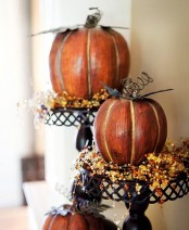 metal stands with faux pumpkins and beads that imitate berries are nice vintage rustic decorations to rock