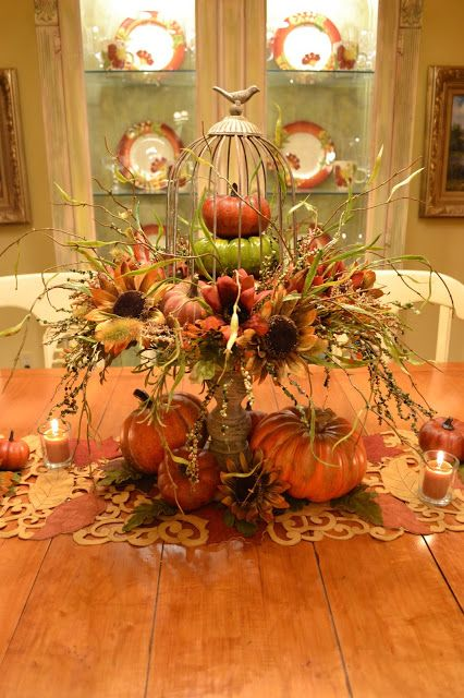 a vintage stand with faux pumpkins, faux blooms, grasses and twigs, plus candles around for a rustic centerpiece