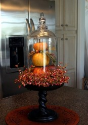 stacked faux pumpkins with fau berries on a wooden stand and a cloche is a bold vintage centerpiece with a rustic feel