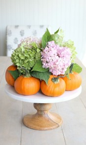 natural orange pumpkins with hydrangeas and leaves on a classic wooden stand is a cool centerpiece
