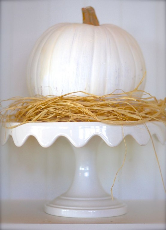 a white pumpkins with hay on a white refined stand for a rustic vintage look in neutrals