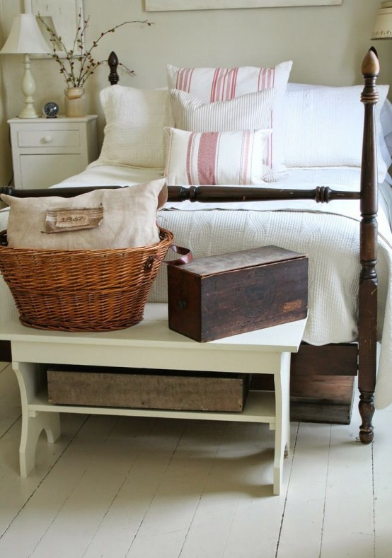 a farmhouse bedroom done with whitewashed wood, vintage painted and stained furniture and boxes and baskets