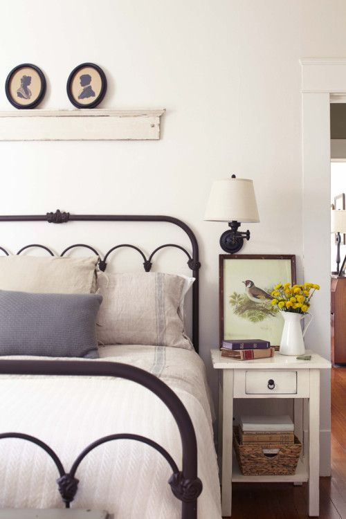 a simple farmhouse bedroom with vintage furniture, a metal bed and a nigthstand with a basket