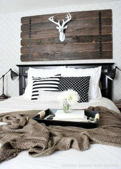 a farmhouse bedroom with a weathered wood art with a fake deer head, a black bed, vintage metal lamps