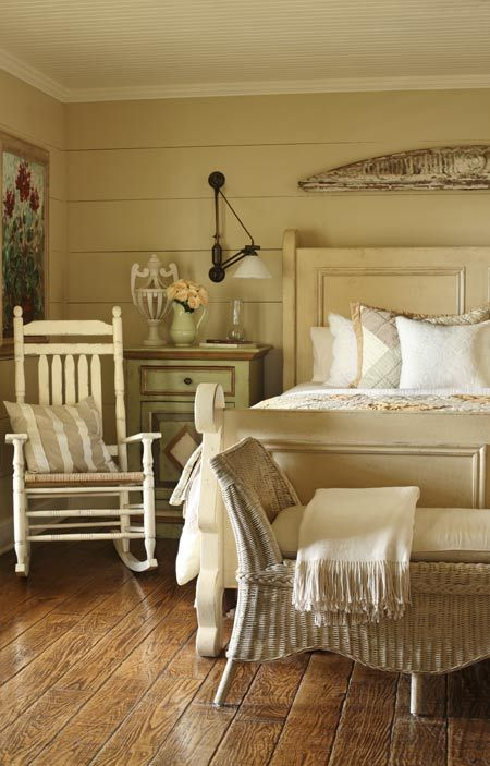 a neutral vintage farmhouse bedroom with vintage furntiure, artworks and lamps