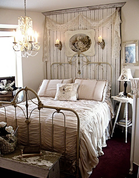 an exquisite vintage farmhouse bedroom with whitewashed furniture, lamps and chests, lace and artworks