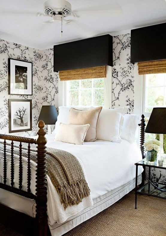 a chic farmhouse bedroom done in black, white and neutrals, with wooden shades and a wooden bed