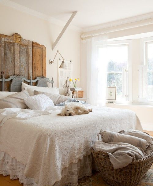 a farmhouse bedroom with a vintage door headboard, a basket for storage and much natural light