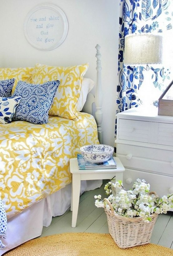 a pastel farmhouse bedroom in blues and yellows, with many prints and whitewashed furniture