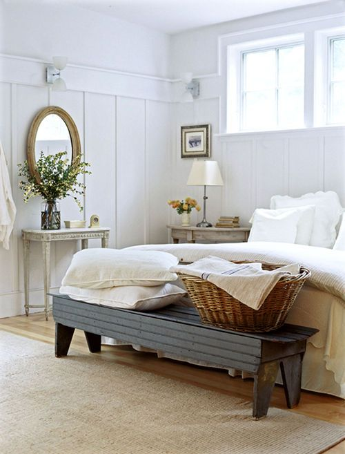 a neutral farmhouse bedroom with weathered wood nightstands, a refined vanity, a dark bench and a basket